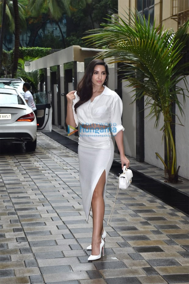Nora Fatehi mesmerizes in all-white look; dons crop top, high waist skirt, pumps and sling bag